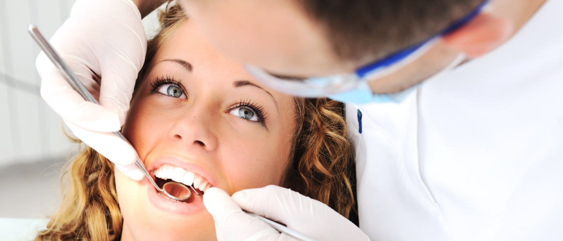 young_girl_getting_teeth_checked_by_dentist